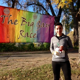 Elizabeth, post-race, standing in front of the big gay race rainbow banner