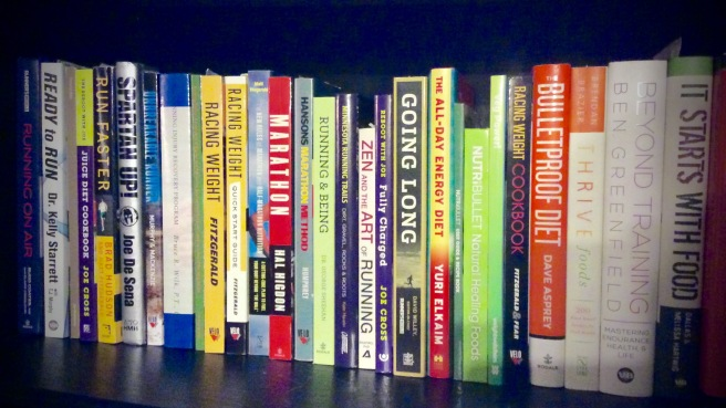 Several books about running and nutrition on a shelf