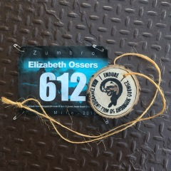 Race bib Elizabeth Ossers 612 and Zumbro 50 mile wooden medal on a metal surface