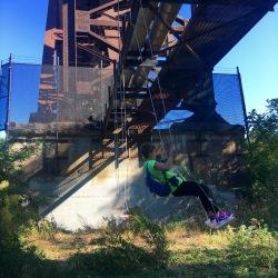 Jen standing on a swing under a metal bridge