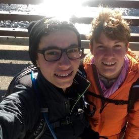 Elizabeth and Jen, on a bridge with sun shining on a creek